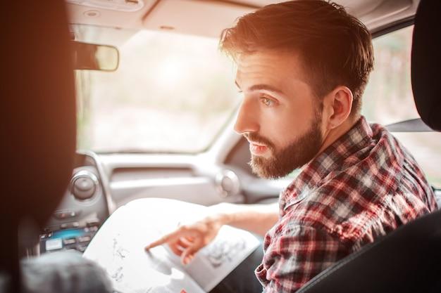 Facet trzyma mapę w dłoniach i wskazuje na nią. rozmawia z człowiekiem siedzącym przy sterze. facet ma miłą rozmowę.