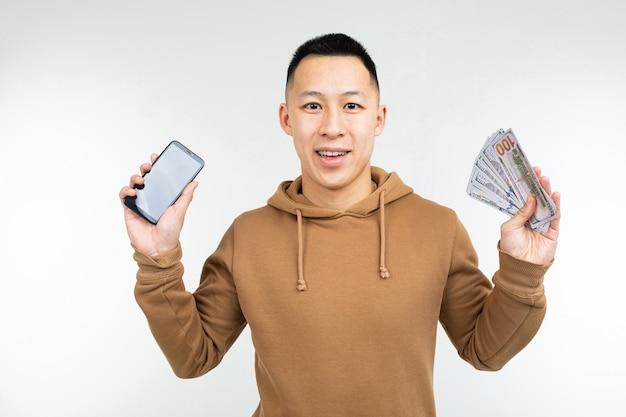 Facet trzyma nagrodę w postaci pieniędzy i telefonu z makietą na białym tle.