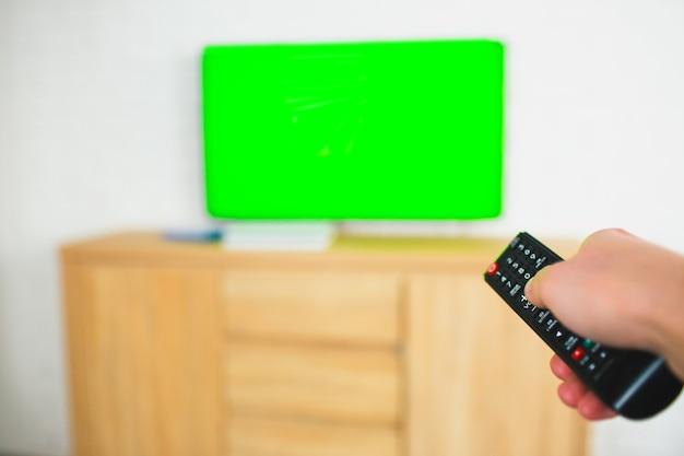 Facet trzyma pilota w dłoni i przykłada go do telewizora z zielonym ekranem