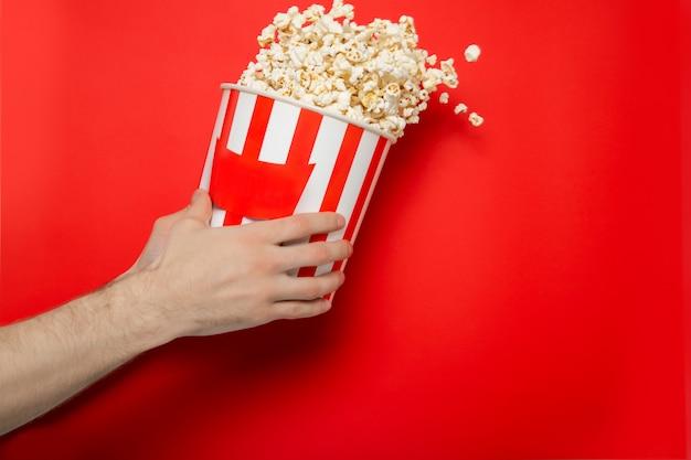 Facet trzyma popcorn w dłoniach na czerwonej ścianie. miejsce na tekst.
