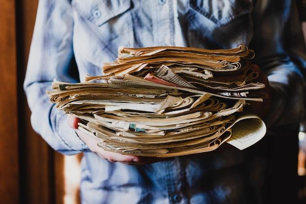 Facet trzyma stos starych gazet z książkami, zbliżenie bez twarzy. kolekcja starych gazet