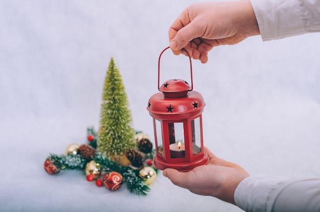 Facet trzyma w rękach lampę ze świecami