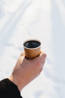 Facet trzyma w ręku papierową filiżankę kawy w śnieżnym lesie