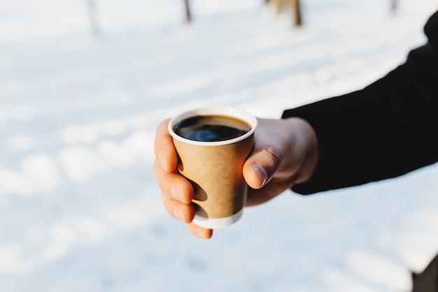 Facet trzyma w ręku papierową filiżankę kawy w zaśnieżonym lesie.