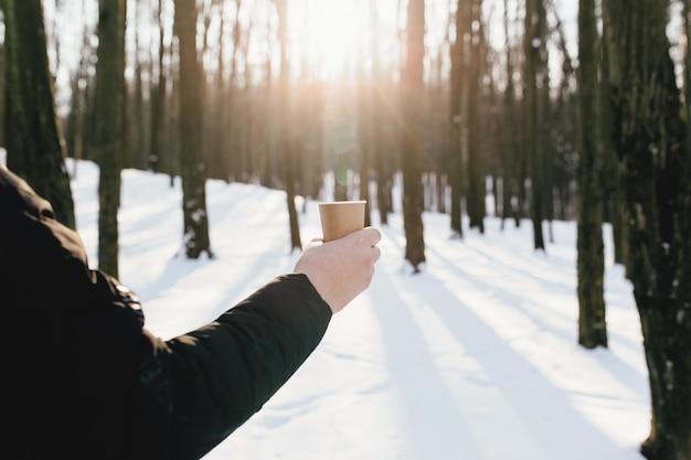 Facet trzyma w ręku papierowy kubek z kawą w zaśnieżonym lesie