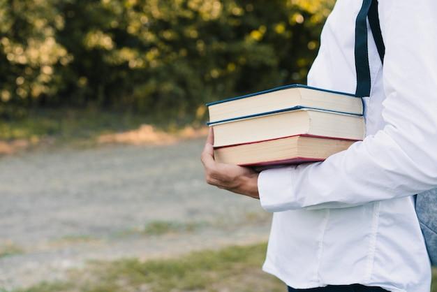 Facet trzymający książki w ręku