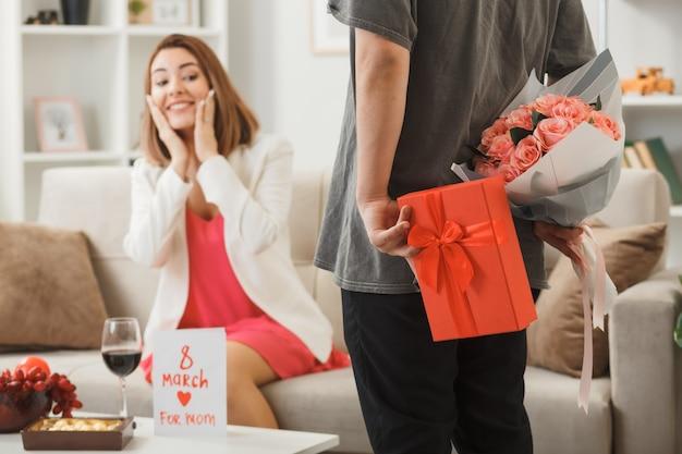 Facet trzymający prezent z bukietem uśmiechnięta kobieta kładąca ręce na policzkach siedząca na kanapie w szczęśliwy dzień kobiet w salonie