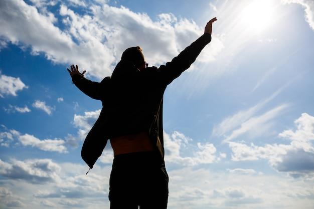 Facet turystyczny freelancer na tle błękitnego nieba z białymi chmurami, jasny słoneczny dzień, natura i wolność człowieka