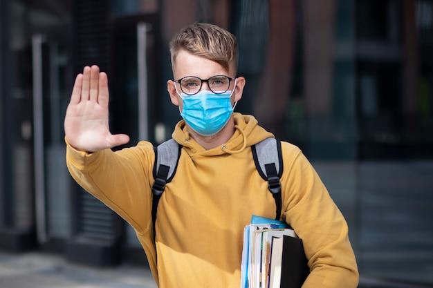 Facet, uczeń, chłopiec, młody człowiek w ochronnej masce medycznej i okularach na twarzy na zewnątrz uniwersytet z książkami, podręczniki pokazują dłoń, dłoń, nie ma znaku. wirus, koncepcja koronawirusa pandemicznego. covid-19