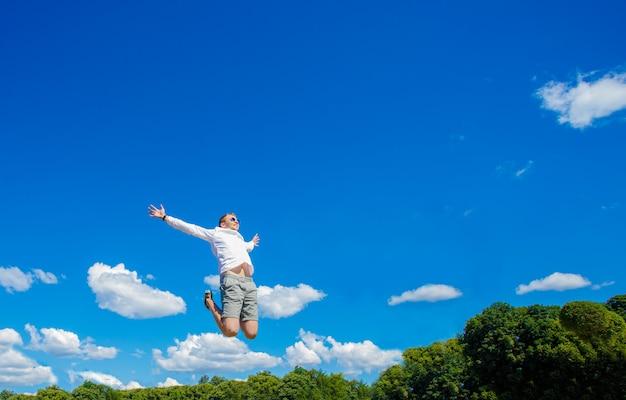 Facet unosi się w powietrzu. facet unosi się w powietrzu na tle fontanny