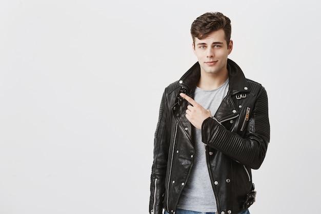 Facet uśmiecha się delikatnie w czarnej skórzanej kurtce wskazuje palcem wskazującym w przestrzeni kopii tekstu reklamowego lub promocyjnego. przystojny stylowy mężczyzna o ciemnych włosach i niebieskich oczach wskazuje na odległość