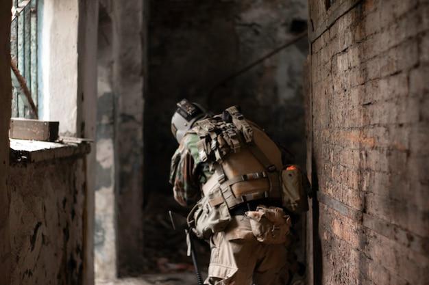 Facet w amerykańskim mundurze wojskowym w starym opuszczonym przejściu porusza się z pistoletem airsoft sports gam