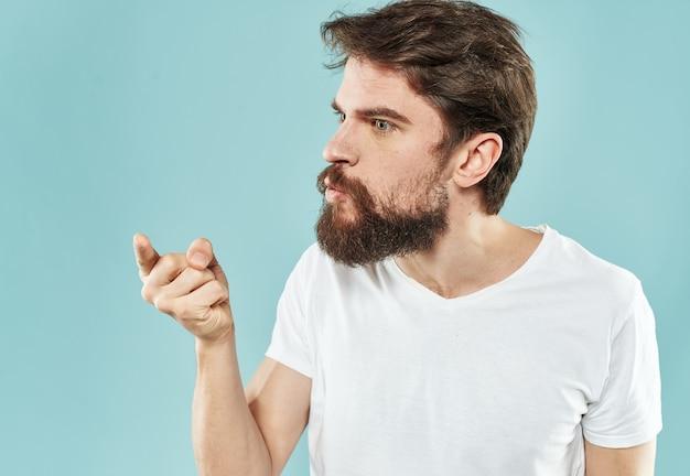 Facet w białej koszulce brunet na niebieskiej ścianie przycięty widok zdziwiony widok z boku.