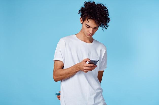 Facet w białej koszulce kręcone włosy telefon w technologii rąk niebieski