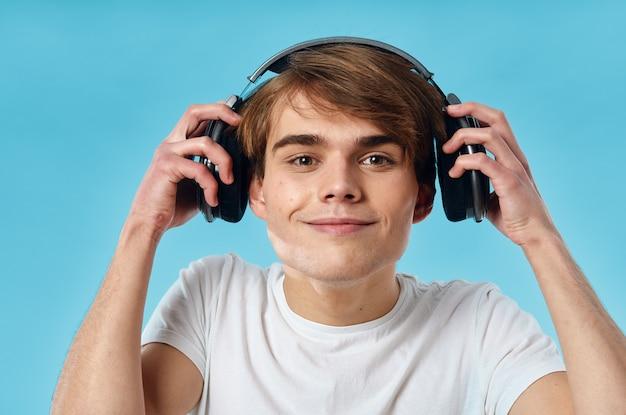Facet w białej koszulce nosi słuchawki emocje muzyka technologia niebieskie tło