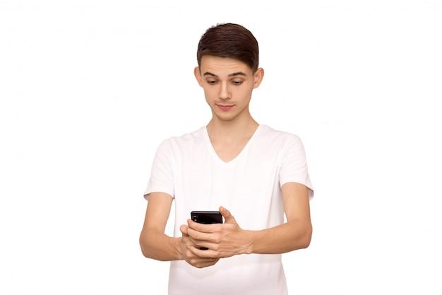 Facet w białej koszulce, patrzy w telefon, izoluje