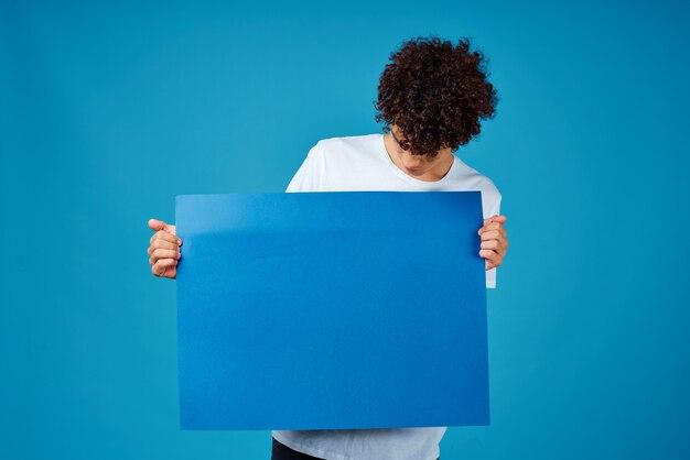 Facet w białej koszulce z niebieskim plakatem
