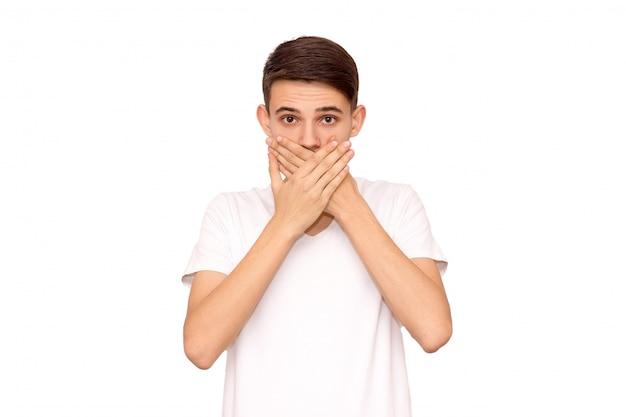 Facet w białej koszulce zakrywa usta dłońmi i izoluje