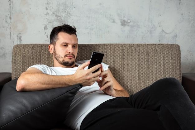 Facet w białej koszuli leży na kanapie i siedzi w telefonie.