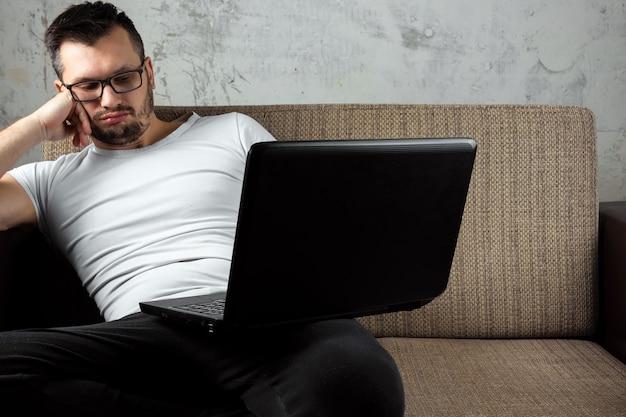 Facet w białej koszuli siedzi na kanapie, zasnął w pracy na laptopie.