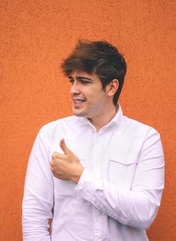 Facet w białej koszuli uśmiechnięty i unoszący się kciuk na pomarańczowej ścianie