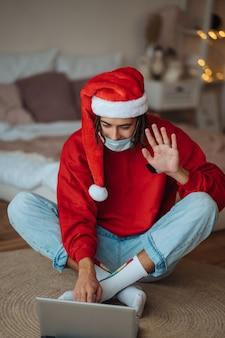 Facet w czapce świętego mikołaja w pobliżu laptopa prowadzi rozmowy wideo. boże narodzenie w izolacji w domu. dystans społeczny na wakacje.