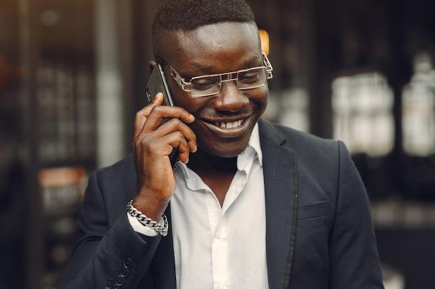 Facet w czarnym garniturze. mężczyzna z telefonem komórkowym. biznesmen w biurze.
