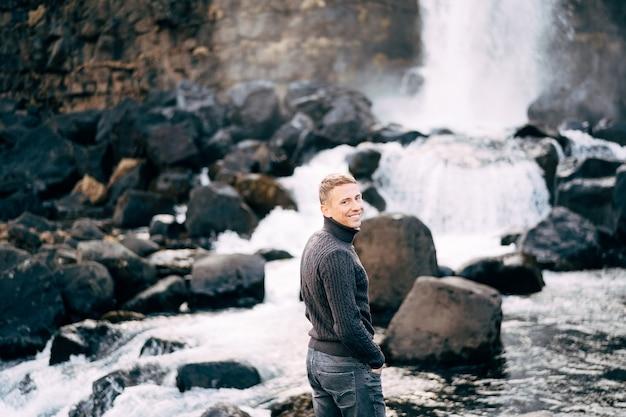 Facet w czarnym swetrze z dzianiny stoi na skałach