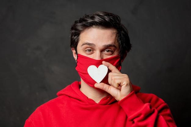 Facet w czerwonej bluzie i masce na twarzy trzyma kształt serca na ciemnej ścianie