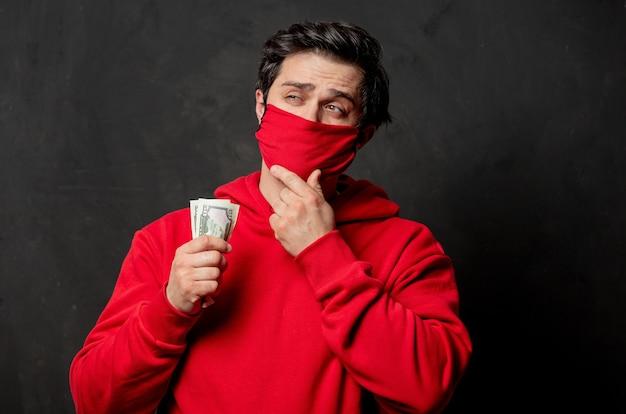 Facet w czerwonej bluzie i masce na twarzy trzyma pieniądze w dłoni na ciemnej ścianie