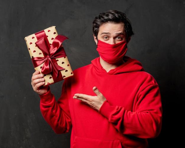 Facet w czerwonej bluzie i masce na twarzy trzyma pudełko na ciemnej ścianie
