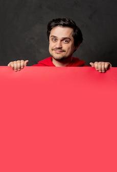 Facet w czerwonej bluzie trzyma różowy sztandar na ciemnej ścianie