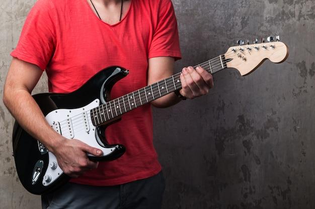 Facet w czerwonej koszuli z gitarą elektryczną