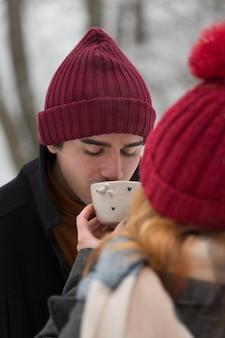 Facet w czerwonym kapeluszu popijając filiżankę herbaty