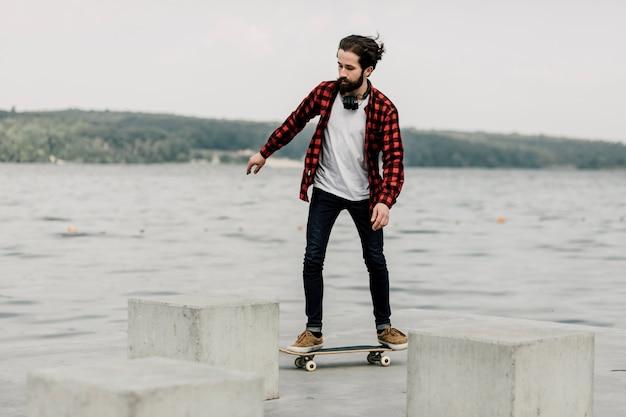 Facet w flaneli na deskorolce nad jeziorem