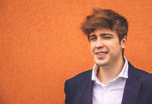 Facet w garniturze uśmiechnięty na pomarańczowej ścianie