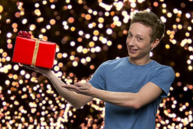 Facet w koszulce pokazuje czerwone pudełko na prezent