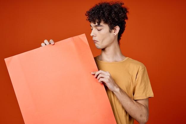 Facet w koszulce trzymający pomarańczowy plakat