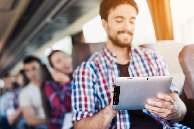 Facet w koszuli siedzi w autobusie i patrzy w tablet