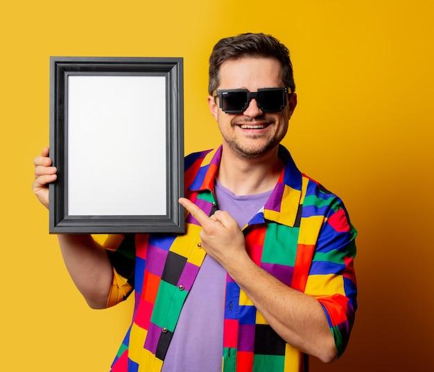 Facet w koszuli z lat 90. i okularach przeciwsłonecznych z ramką na zdjęcie