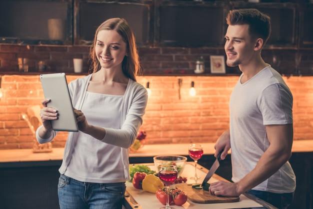 Facet w kuchni podczas gdy jego dziewczyna pokazuje on pastylkę.