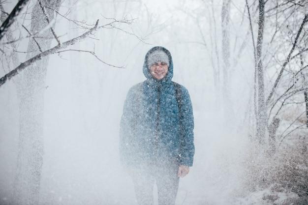 Facet w kurtce z kapturem stoi w zaśnieżonym lesie, śnieg pada na niego z góry.