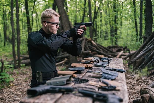 Facet w lesie testuje swoją broń do strzelania do sportu