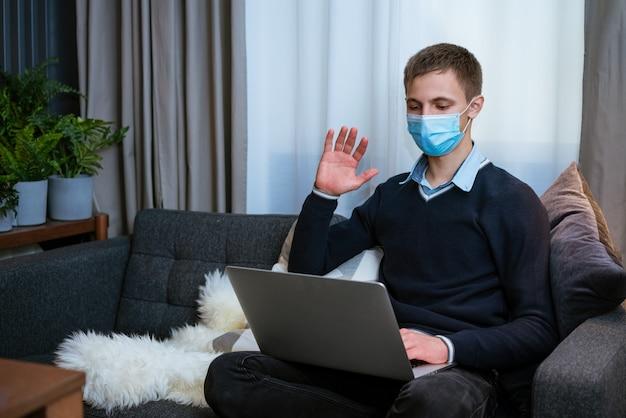 Facet w masce medycznej na kanapie z laptopem komunikuje się za pośrednictwem komunikacji wideo online