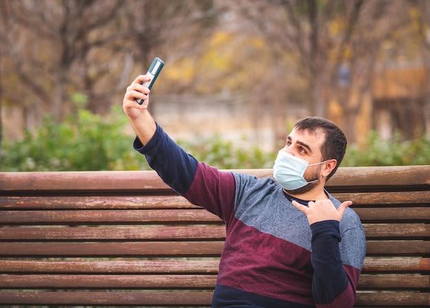 Facet w masce ochronnej robi selfie na ławce w parku o zachodzie słońca
