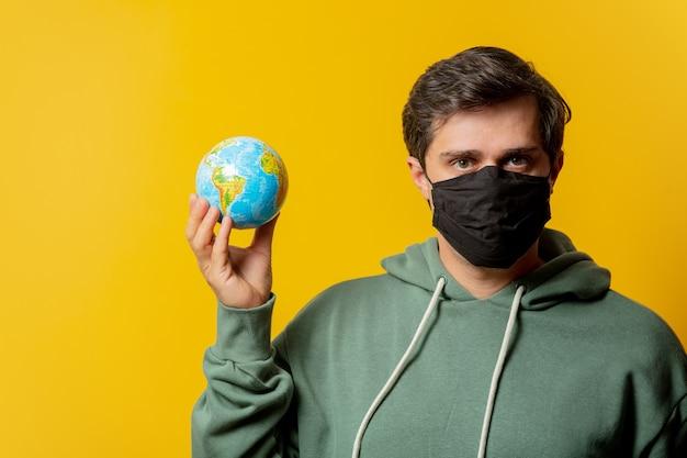 Facet w masce twarzy trzyma kulę ziemską na żółto