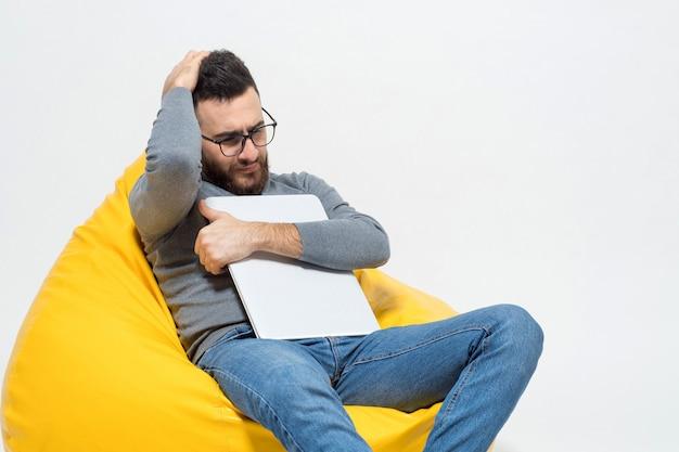 Facet w myślach siedząc na żółtym pufowym krześle