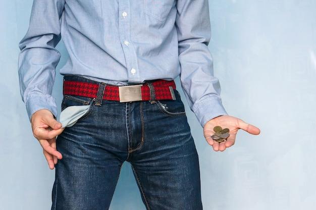 Facet w niebieskich dżinsach wywrócił na lewą stronę puste kieszenie, demonstrując niespójność biedy i niewypłacalności. niezdolność do spłaty swoich długów