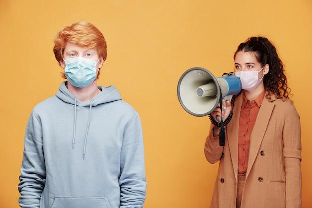 Facet w niebieskiej bluzie i masce stoi z młodą menadżerką w formalnym stroju, krzyczącą na niego przez megafon