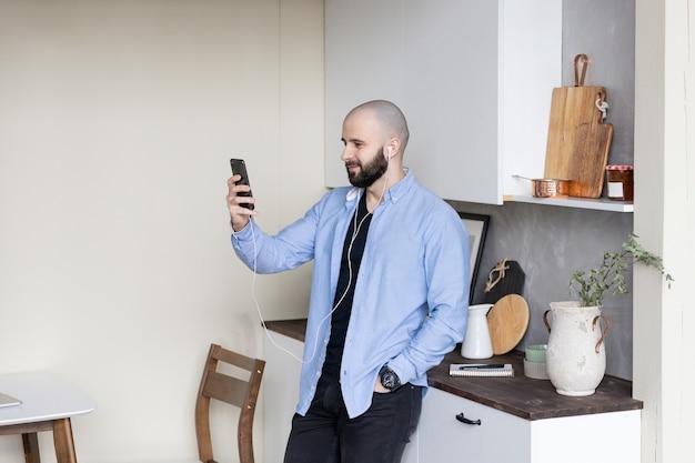 Facet w niebieskiej koszuli i czarnych dżinsach rozmawia przez telefon w domu przez łącze wideo. pojęcie pracy na zlecenie